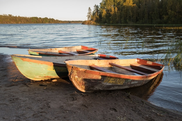 Old shabby wooden fishing colorful boats on the lake shore during sunset, autumn forest on background