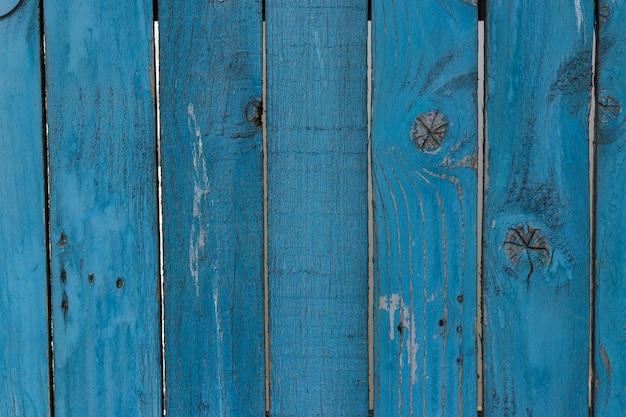 ひびの入った青い色のペンキ、農村部の田舎の面で古いぼろぼろの木板