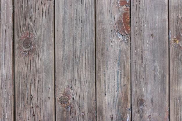 Старые ветхие деревянные доски с потрескавшейся краской коричневого цвета, фон сельской местности