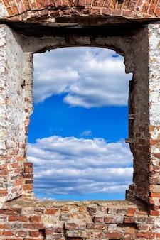 空と雲のあるレンガの壁にある古い粉々になった窓。高品質の写真