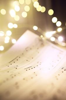 Старый лист с рождественскими нотами в качестве фона против размытых огней. рождественская музыкальная концепция
