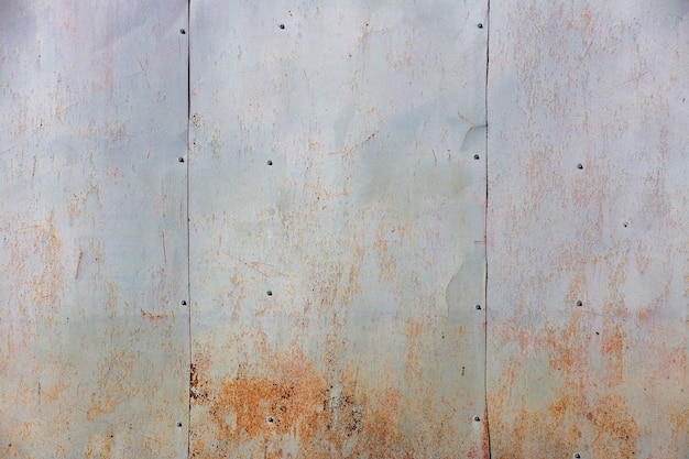 Old sheets of iron on the wall of the house with remnants of paint and rust background