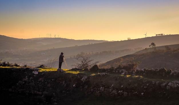 夕暮れ時の山を探している古い羊飼い
