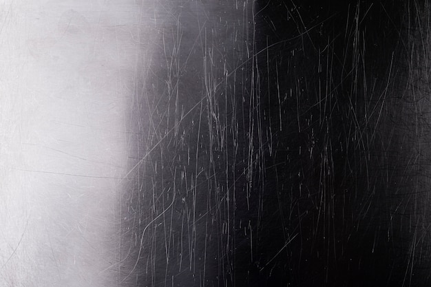Old shiny metal background, dark brushed metal texture with scratches and light gradient