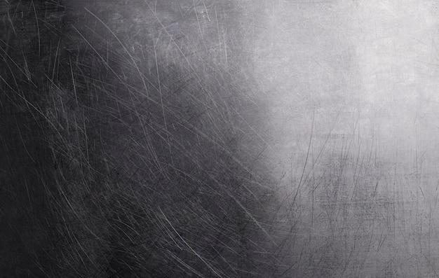 古い光沢のある金属の背景、傷と光のグラデーションで暗いポリッシュメタルテクスチャ