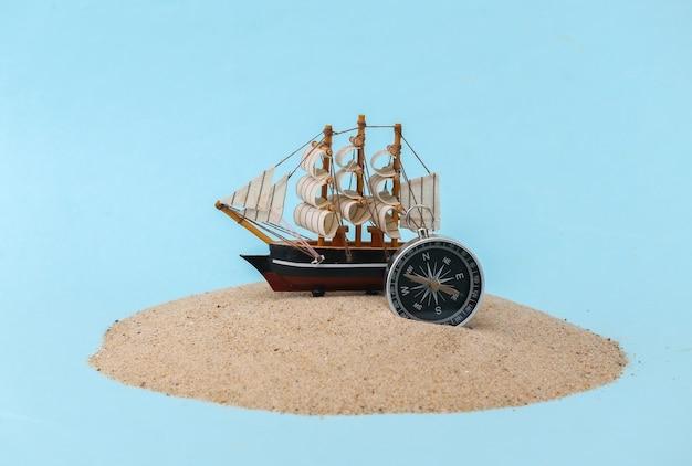 모래 섬에 나침반과 함께 오래 된 배입니다. 모험