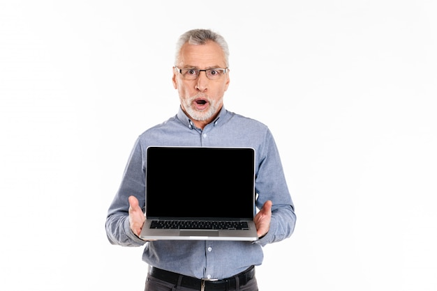 Old shocked man showing laptop with blank screen isolated