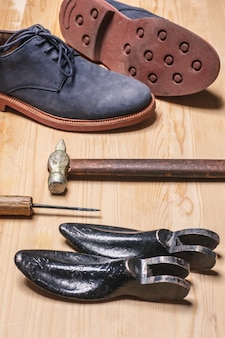 Old shoemaker tools and boots on wooden table