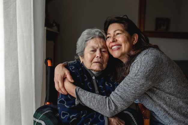 Old sick portrait of woman in wheelchair hugging daughter with positive face. third age, home care concept.