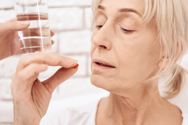 Old sick woman drinking pills