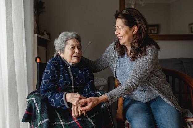 웃는 딸 옆 휠체어에 오래 된 아픈 여자. 세 번째 나이, 홈 케어 개념.