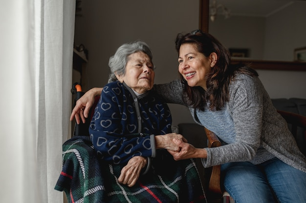 Old sick woman in wheelchair next to smiling daughter. third age, home care concept.