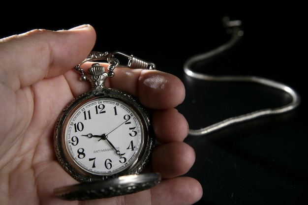 Old silver pocket watch clock on human hand