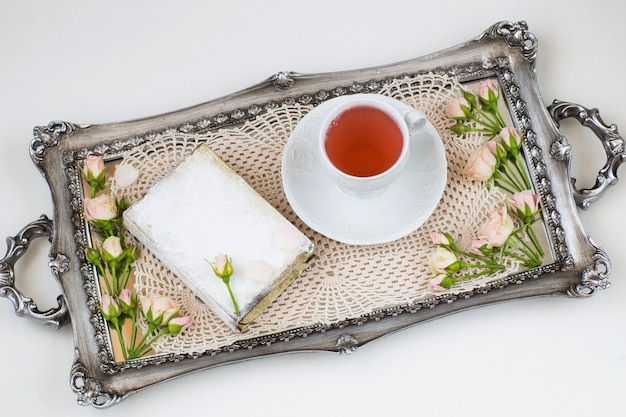 In the old silver tray lace napkin, rosebuds, a cup of tea and a book