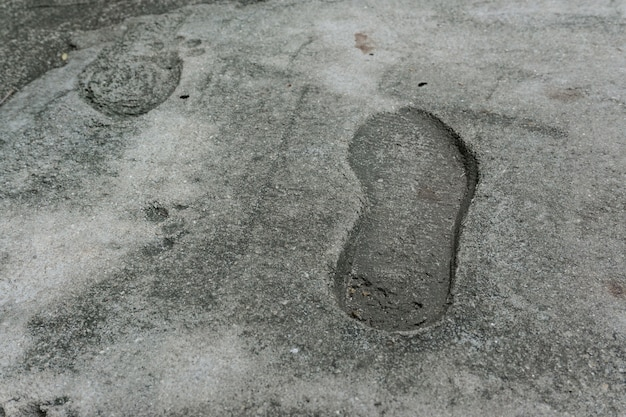 The old single imprint, footprint of shoe or boot on concrete