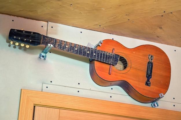 古い6弦の木製ギターが壁に掛かっているドアの向こう側