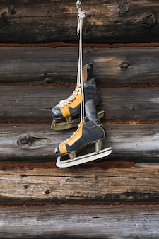 Old skates hanging on wooden wall