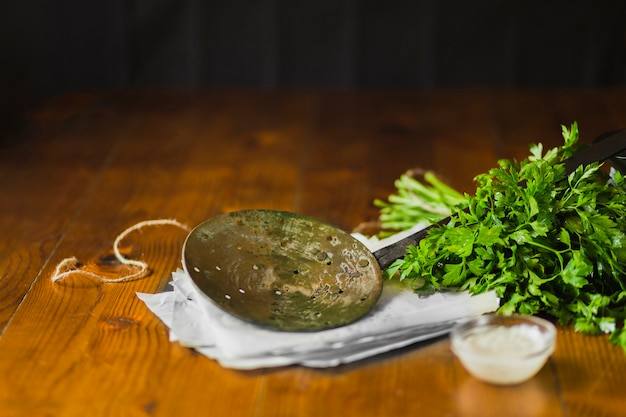 An old skimmer on tissue paper with coriander and garlic dip bowl over the wooden table