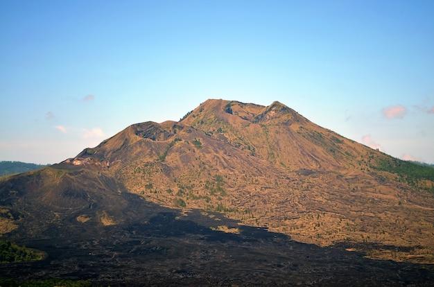 Старый спящий вулкан и сгоревшая земля вокруг после извержения.