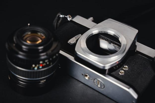 古い一眼レフフィルムカメラと黒い背景のレンズ、写真コンセプト。