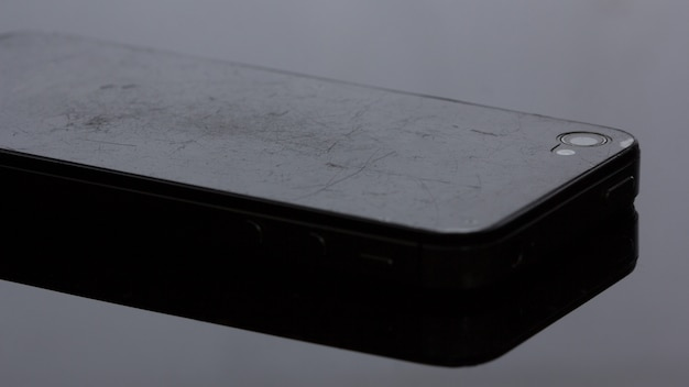 Old smartphone that the film has scratched.on black background
