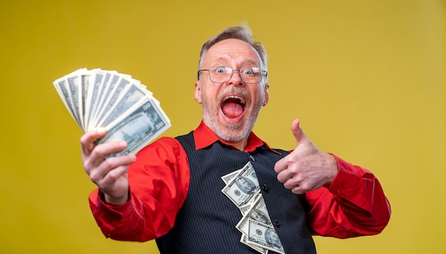Old smiling greyhaired man in eyeglasses holding fan of dollars