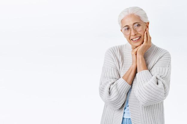 灰色の髪の眼鏡をかけた、笑顔で幸せな年配の女性、喜んで陽気なカメラを見て、顔に触れてニヤリと笑い、孫が遊んでいることを考えます