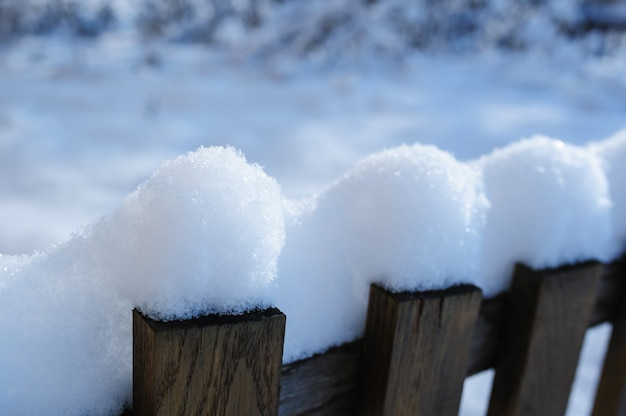 Old snowy fence in village in christmas winter
