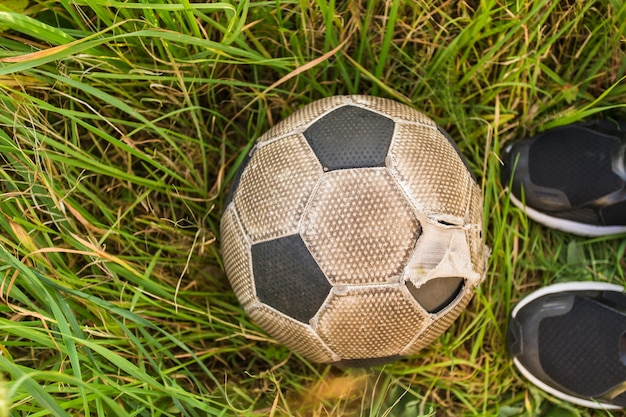 Old soccer ball on the green grass, top view.