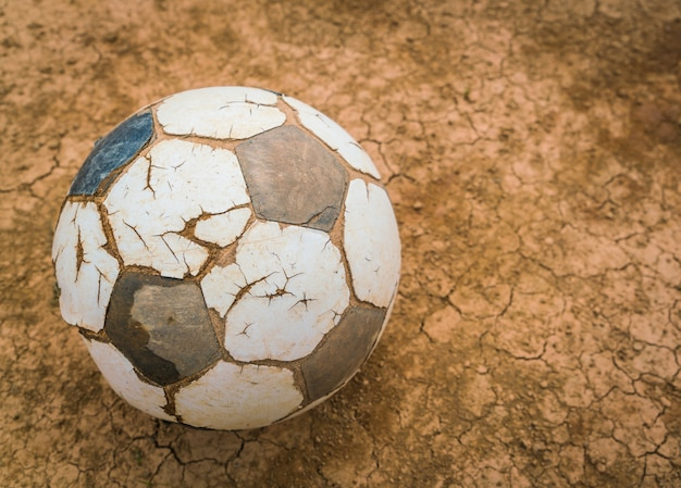 Старый футбольный мяч на сухой и потрескавшейся земля текстуры.