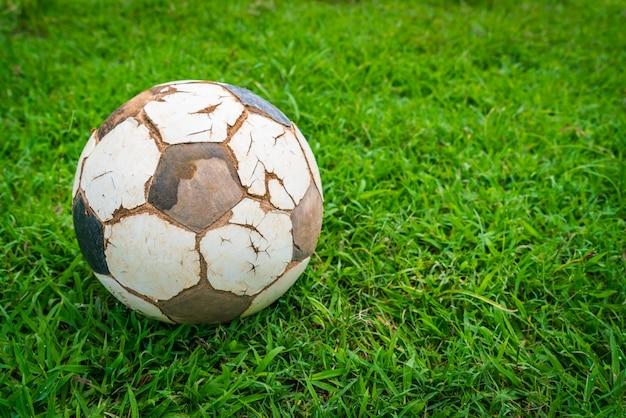 新鮮な春の緑の芝生上の古いサッカーボール