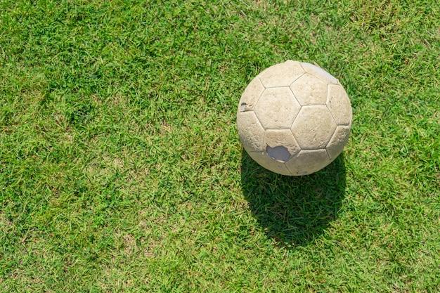 Старый футбольный мяч на зеленой траве футбольного поля. винтажный футбол.