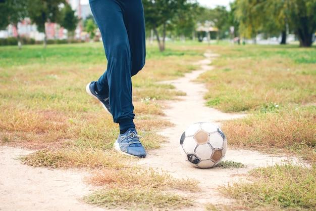 Старый футбольный мяч с подростковой ногой на футбольном поле. выборочный фокус.