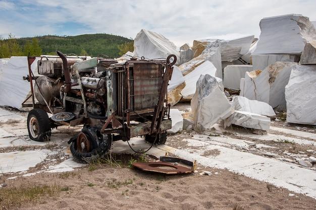Старый советский сломанный ржавый компрессор в заброшенном мраморном карьере с большими белыми мраморными блоками