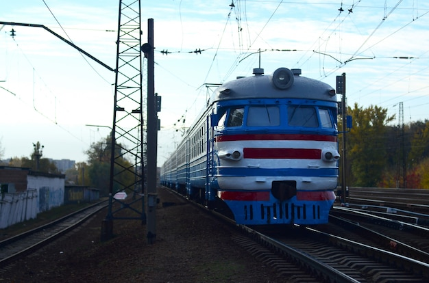 Old soviet electric train with outdated design moving by rail