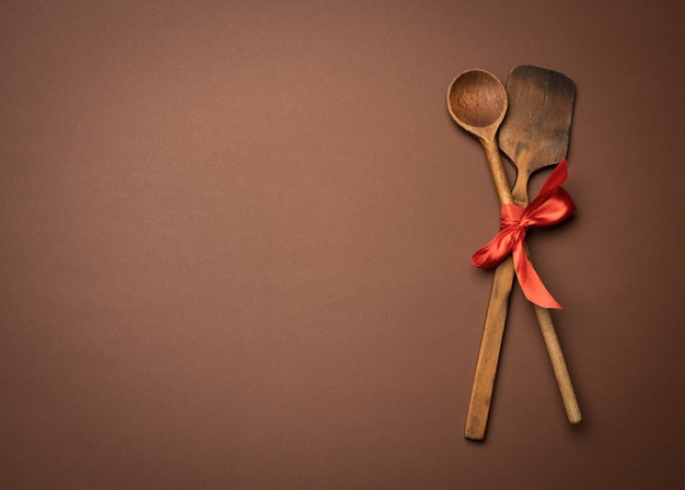 Старая ложка и шпатель, перевязанные красной лентой на коричневом фоне, вид сверху, копия пространства