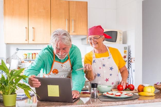 年配の配偶者は、キッチンで一緒に野菜サラダの準備を楽しんでいます。思いやりのある白髪の夫は愛する妻を養う、ロマンチックなデート、幸せな結婚、健康的な食事の概念