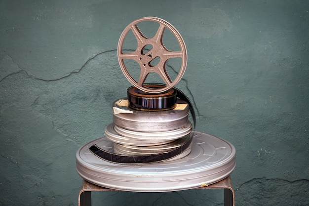 Old stacked vintage movie films of assorted diameters with a projector reel