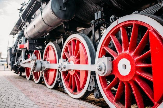 Old steam train, red wheels closeup. vintage locomotive. railway engine, ancient railroad vehicle