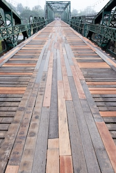 Old steel bridge with the wooden pathway.