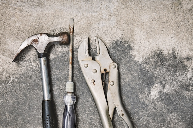 Old steel oxided working tools, hammer, screwdriver and wrench on cement background