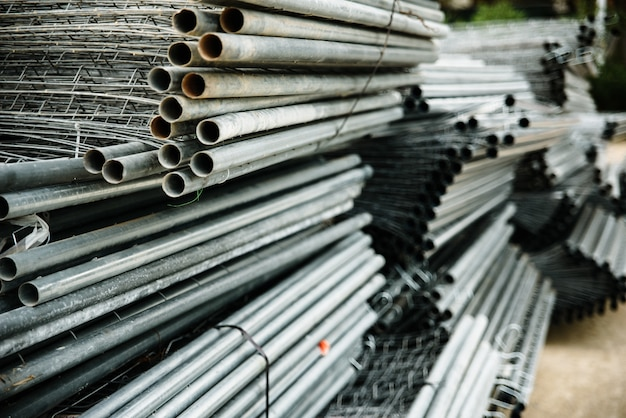 Old steel pipes stacked in an industrial warehouse.