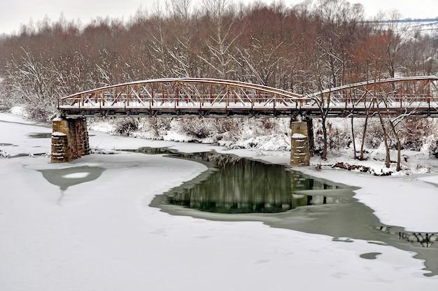 Old steel road bridge over  river  after snowfall