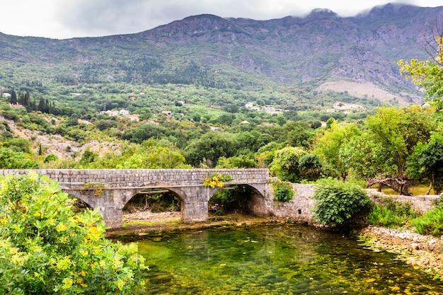 작은 투명 강 위에 오래 된 돌 다리