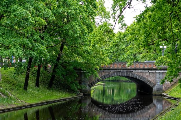 公園の運河に架かる古い石の橋、テキスト用のスペースのある都市の背景