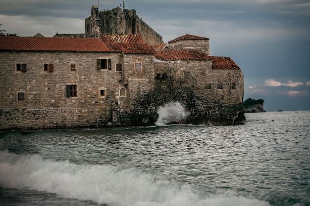 嵐の海で夜遅くに高い崖の上の古い石造りの城塞