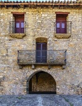 Фасад старого каменного дома, похожий на человеческое лицо с глазами, носом и ртом. аинса, испания,