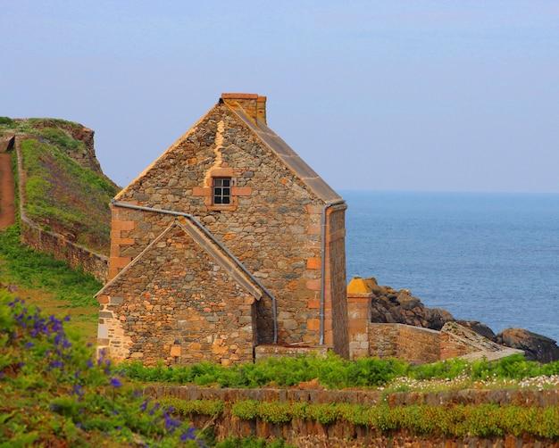 바다 배경에 오래 된 돌 집