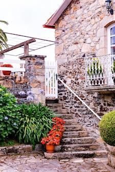 화분에 식물이 있는 계단과 아름다운 발코니가 있는 오래된 석조 집