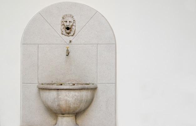 Старая каменная раковина и небольшой кран со скульптурой льва над ним на белом фоне.